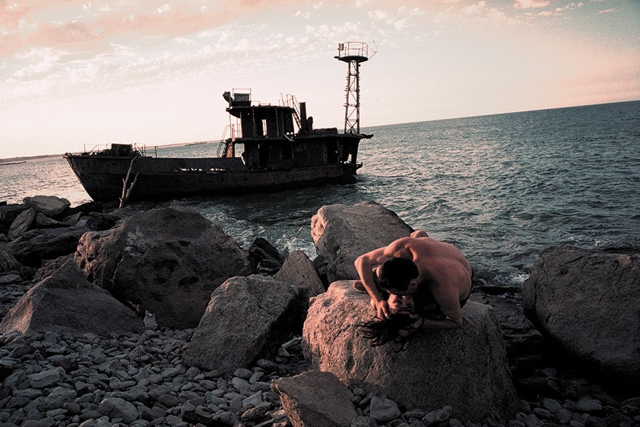 A couple embraces on rocks in front of a boat.