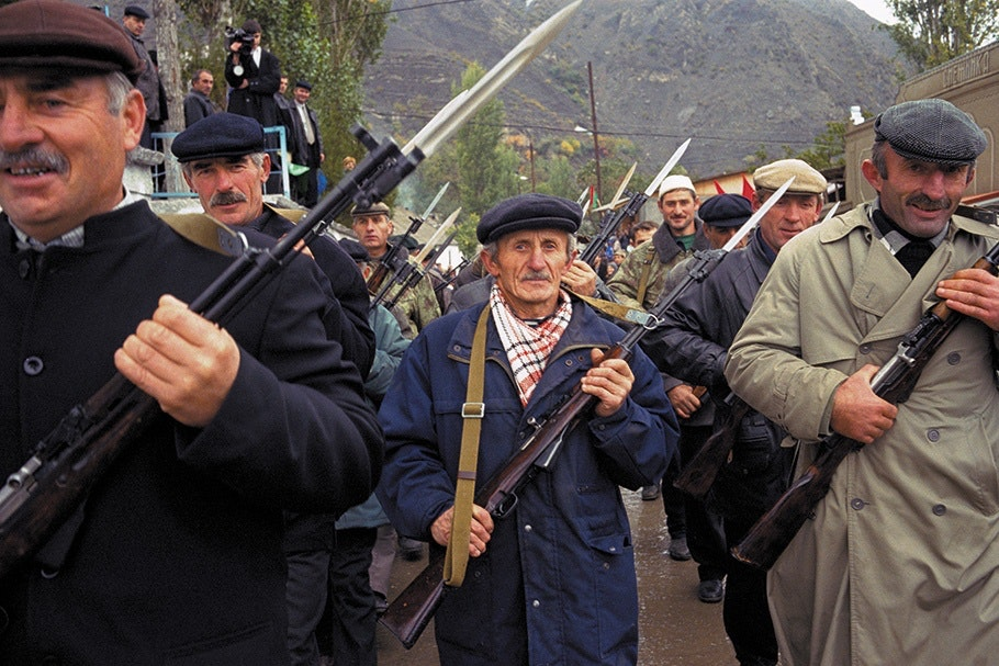 Men in formation with guns.