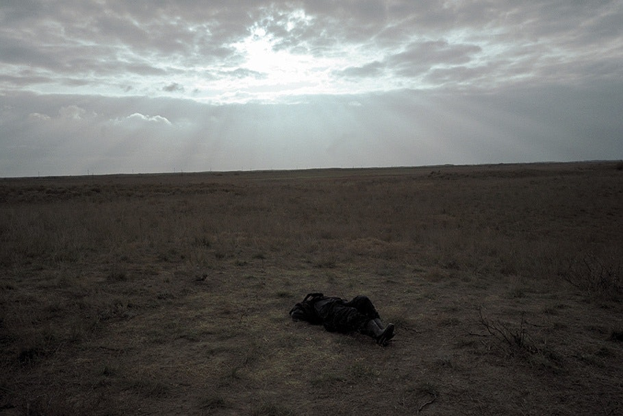 A person laying in a field.