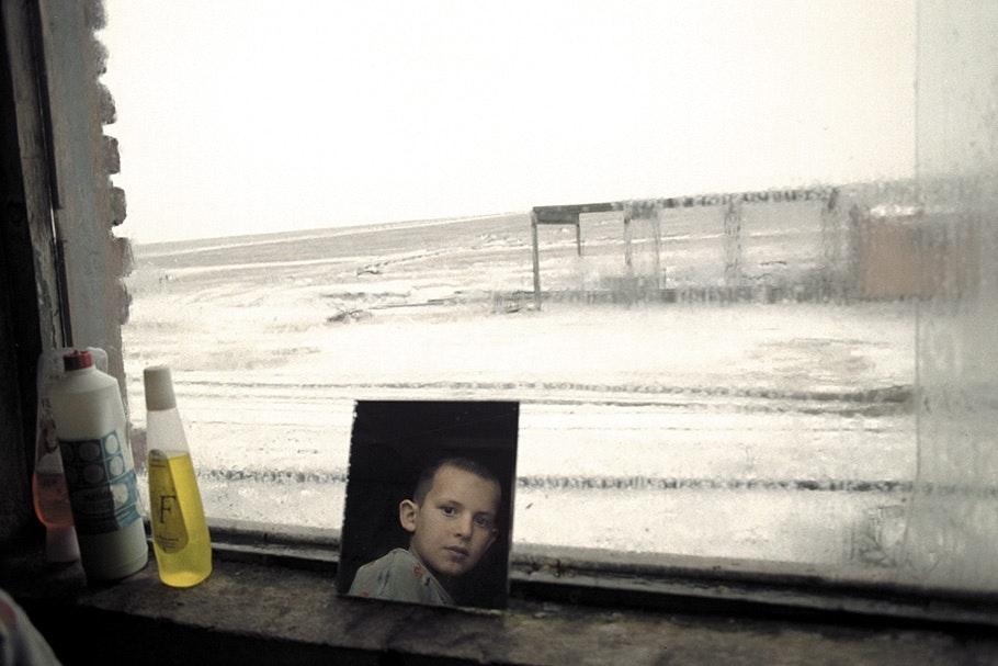 A boy's face in a mirror against a window.