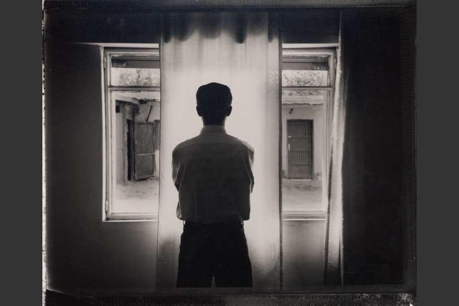 A man silhouetted in front of a window.