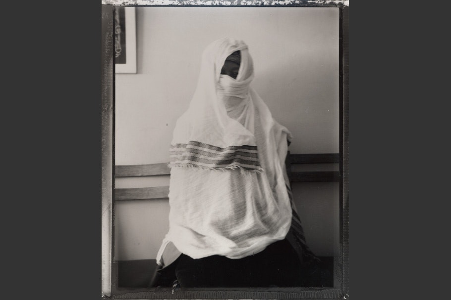 A seated woman wrapped in white fabric.