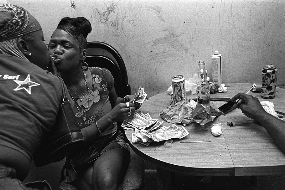 Two women at a table with cash.