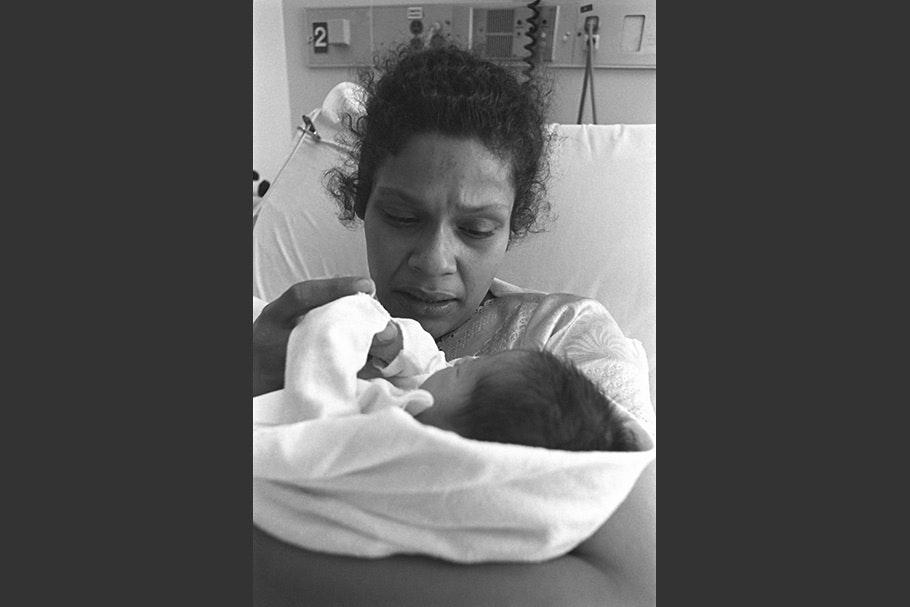 A woman gazing at her newborn.