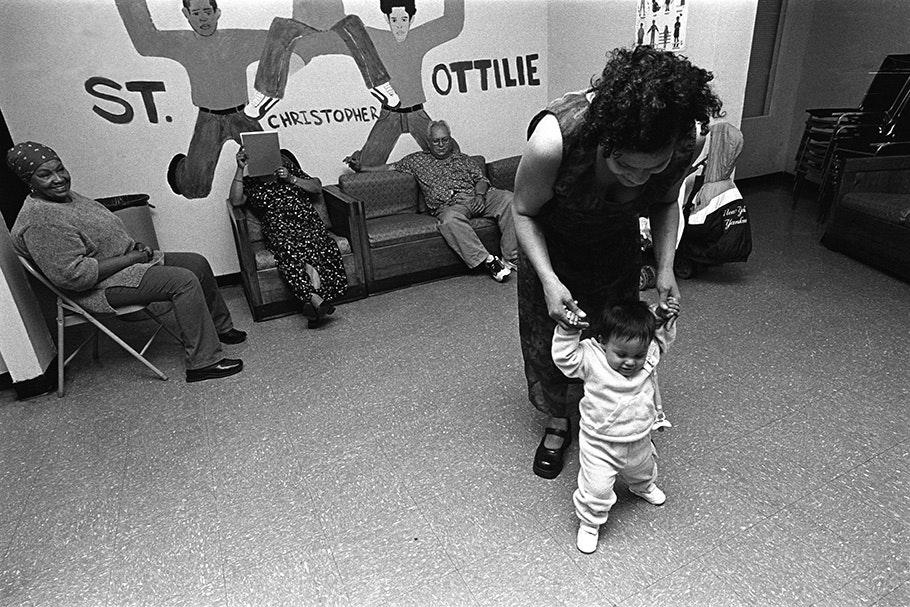 A woman helping an infant walk.