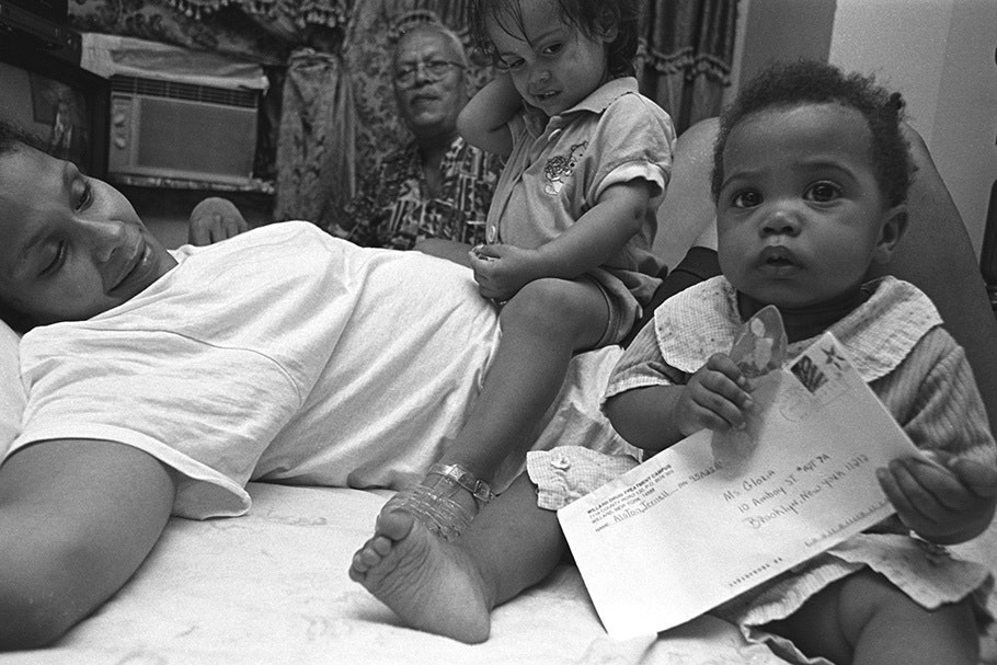 A woman with two children, one holding a letter.