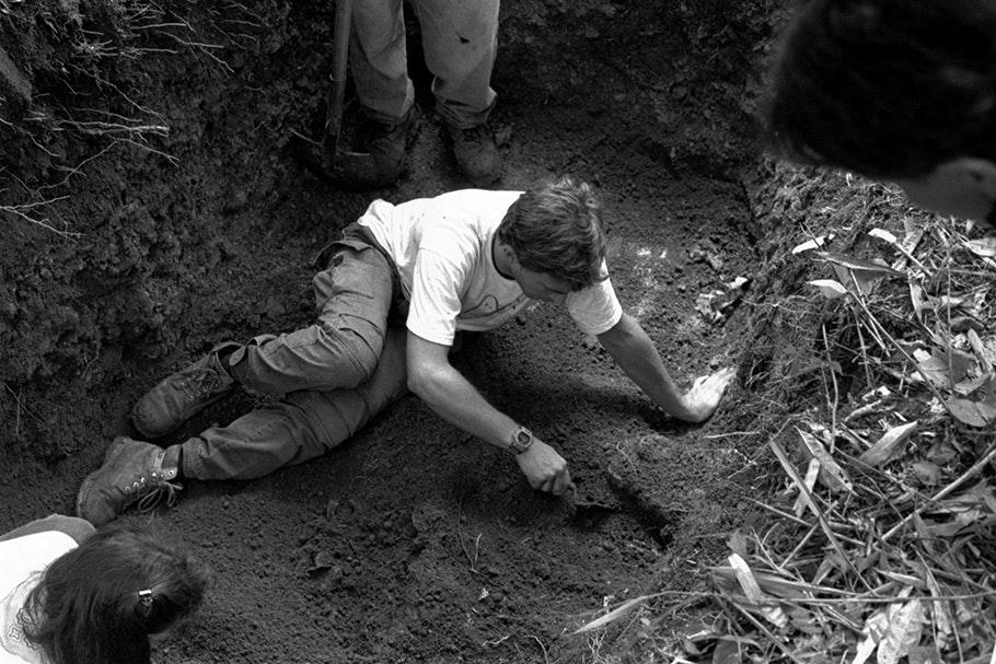 Man seated in dirt, digging.