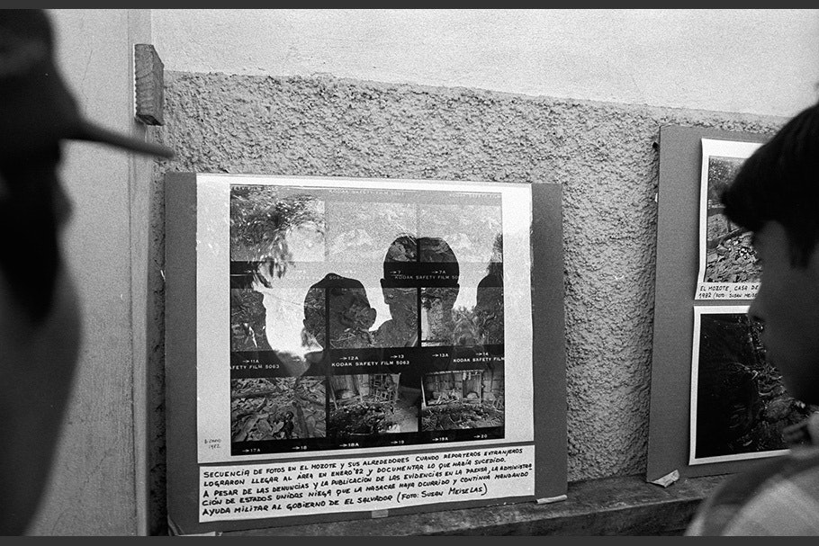 People looking at a contact sheet behind glass.