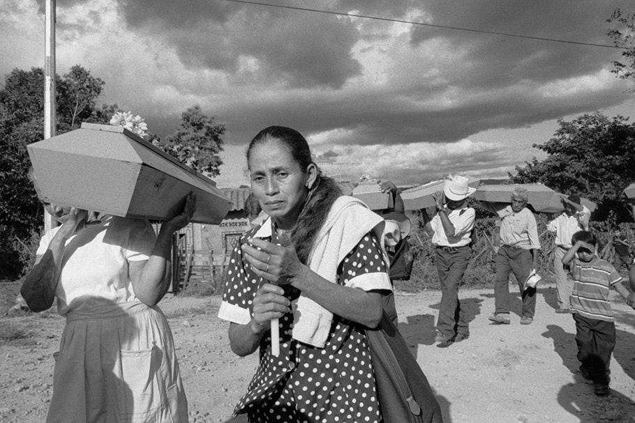 A woman in a polka dot dress walking with a procession of coffins.