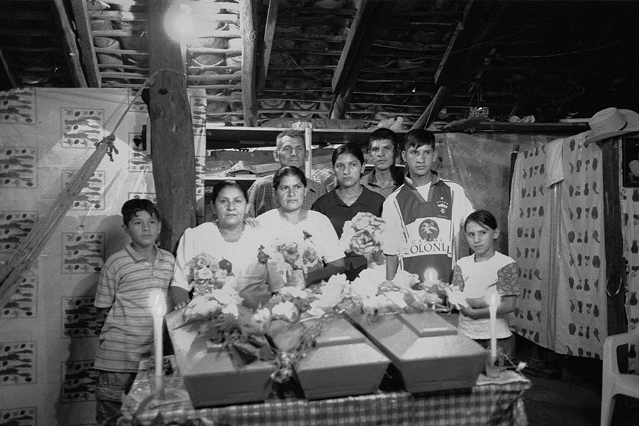 A family posing with three coffins.