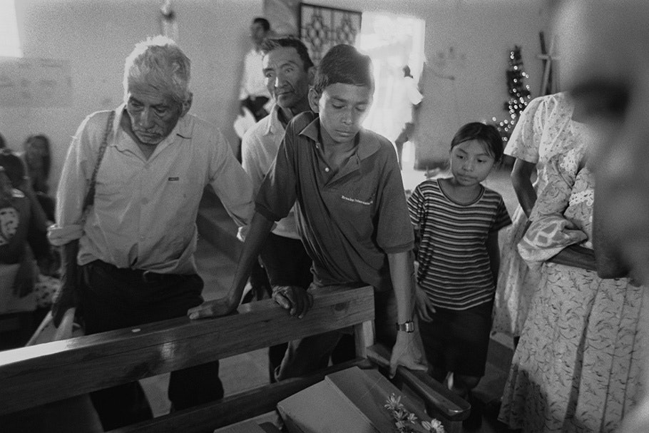 A family looking at a coffin.