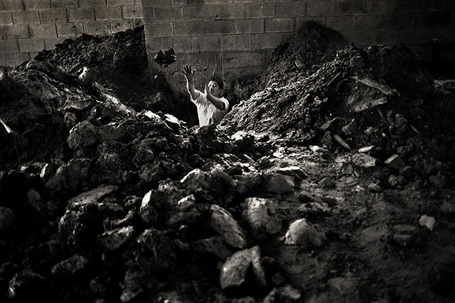 A worker digging a ditch.