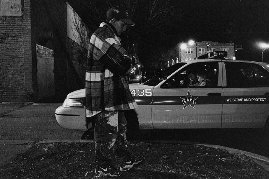 A man walking by a police car at night.