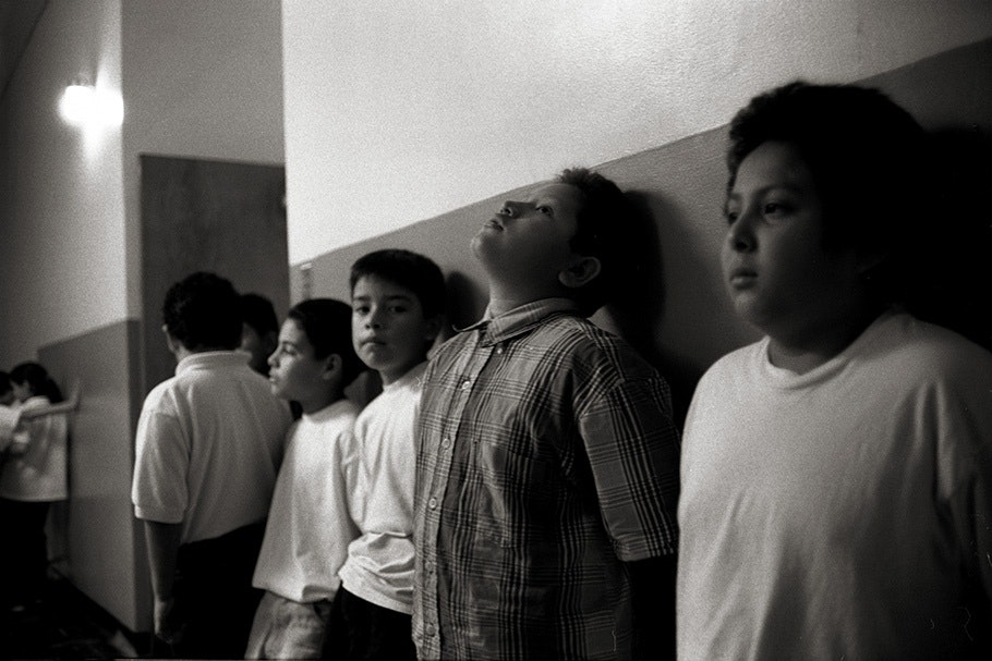 Boys lined up against a school hallway wall.