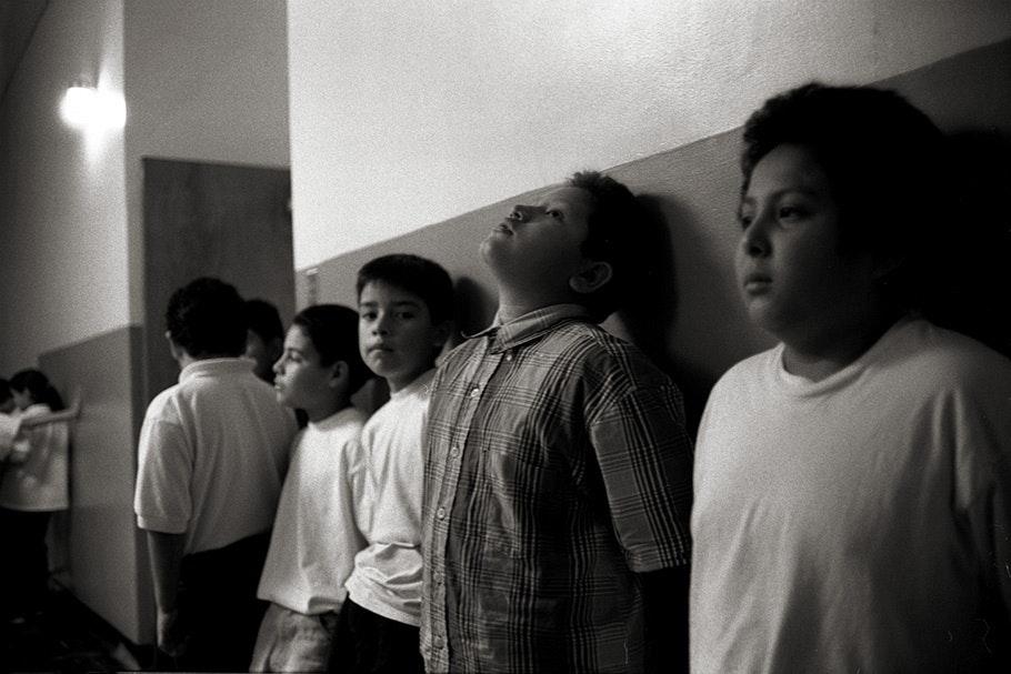 Boys lined up against a school hallway wall.