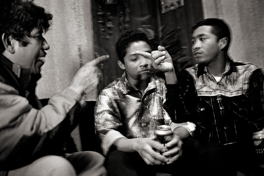 Three men sitting and talking.