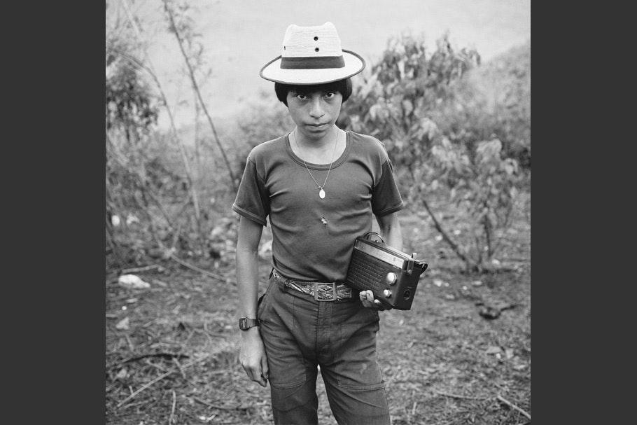 A teenage boy posing with a radio.