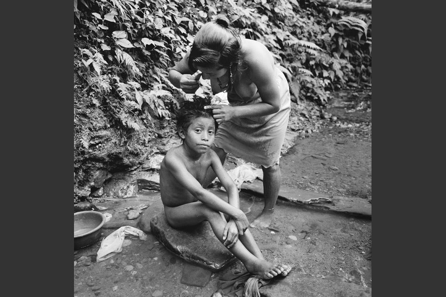 A mother checking her son's hair for lice.
