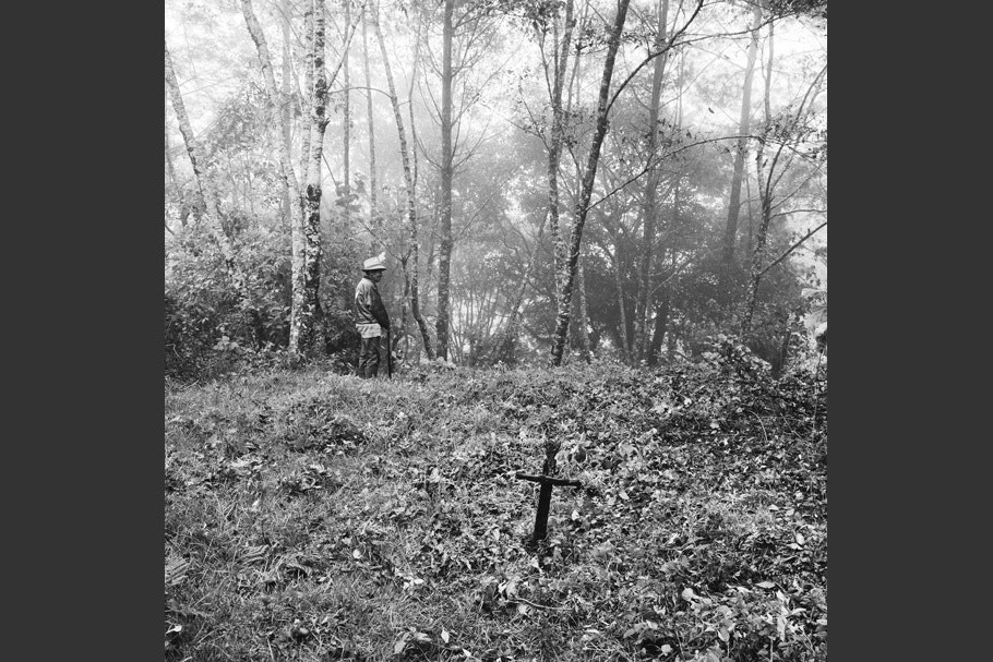 A wooded landscape with a cross and a man.