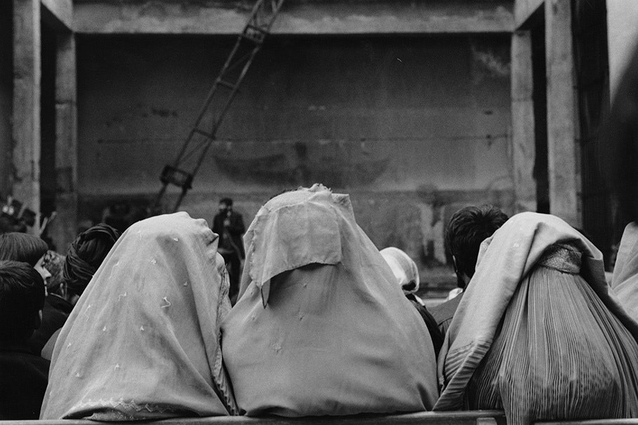 Three women in headscarves at a theater viewed from behind.