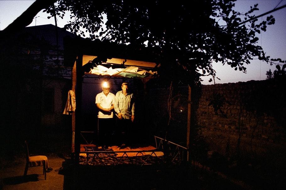 Men praying in an outdoor shelter.