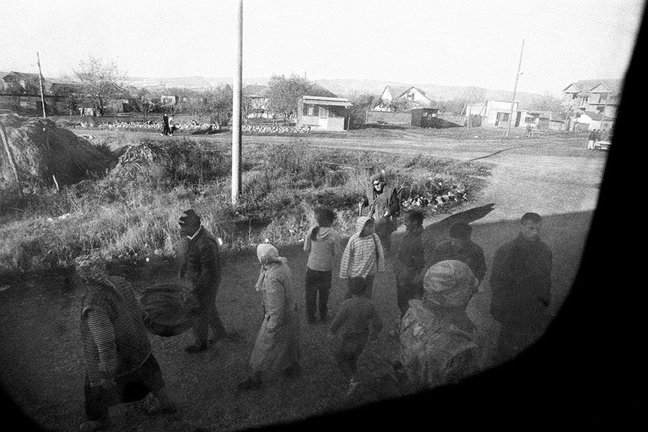 A group of people viewed from a train window.