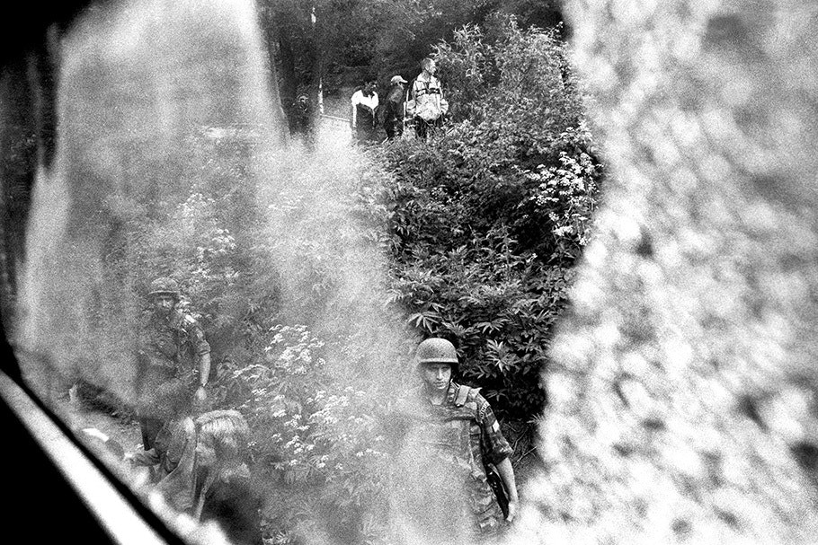 Soldiers and civilians viewed through train window with reflections.