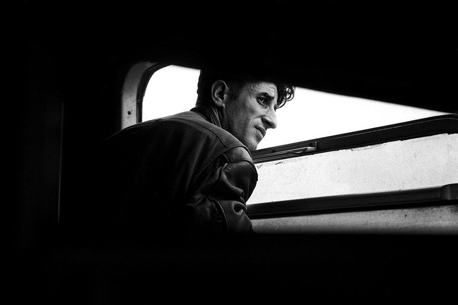 A man looks out a train window.