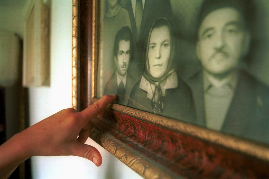 A hand pointing to a framed photograph.