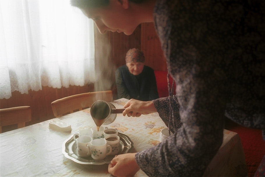 A woman pouring coffee.