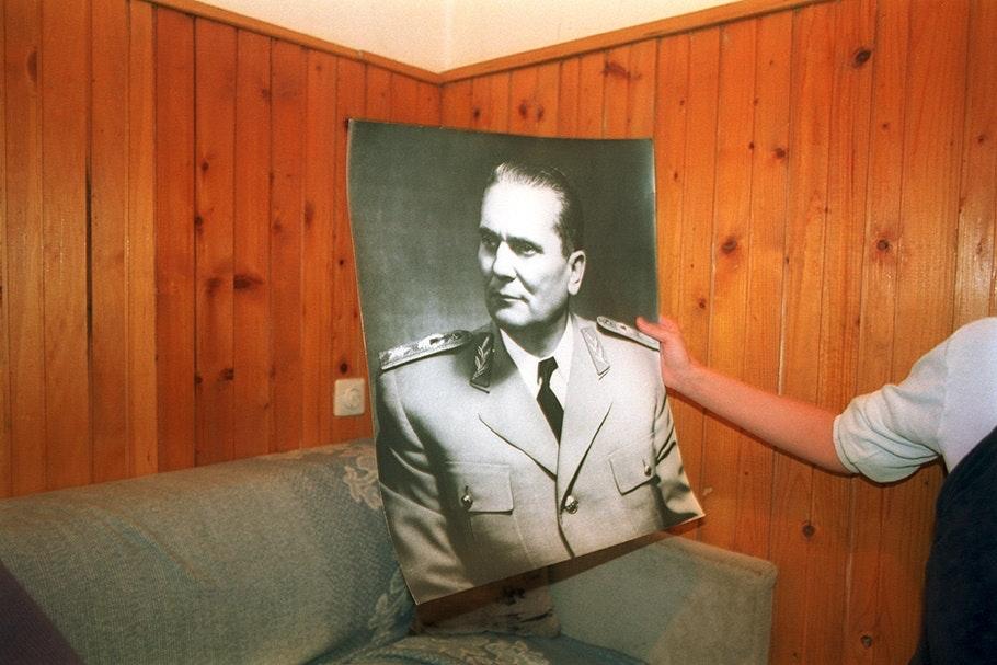 An arm holding a photographic portrait.