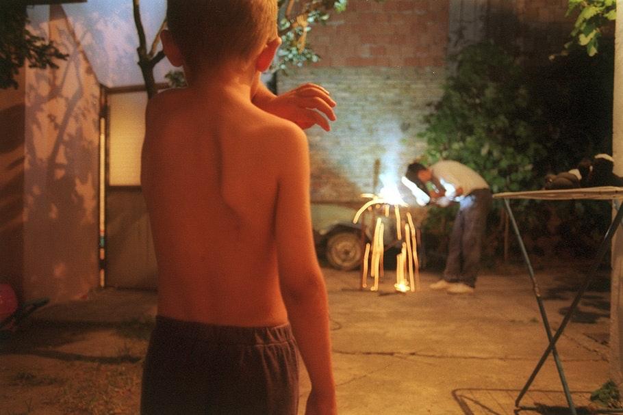 Boy watching a man weld.