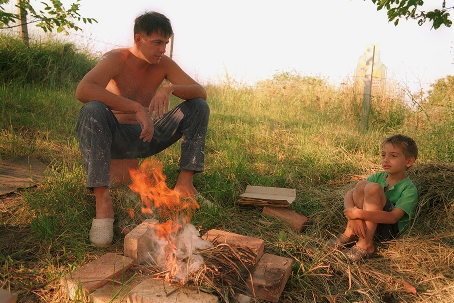 A father and son sit by a fire.
