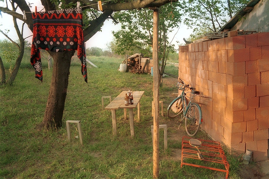 A backyard scene with a table, laundry, and a bicycle.