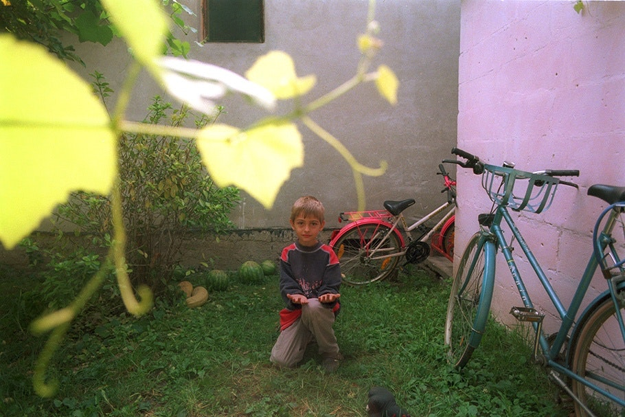 A boy with bicycles and a purple wall.