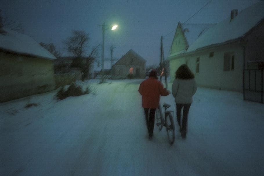 Two women walk down a snowy street at night.