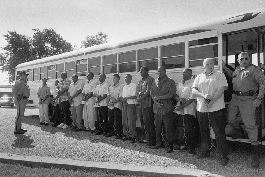 Twelve men in chains in front of a bus with two guards.