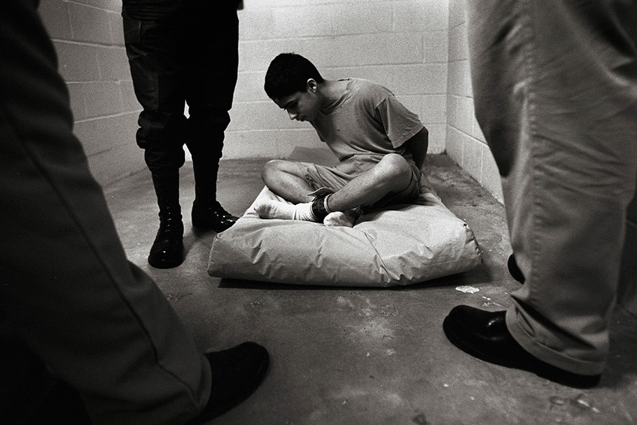 A seated child, handcuffed and surrounded by adults.