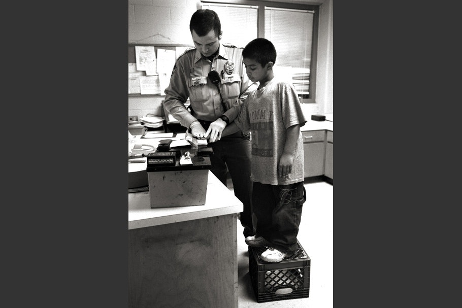 A boy is fingerprinted while standing on a milk crate.