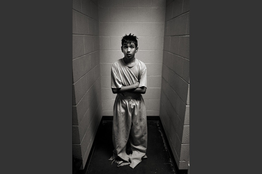 A boy in a cell wearing clothes that are too large.