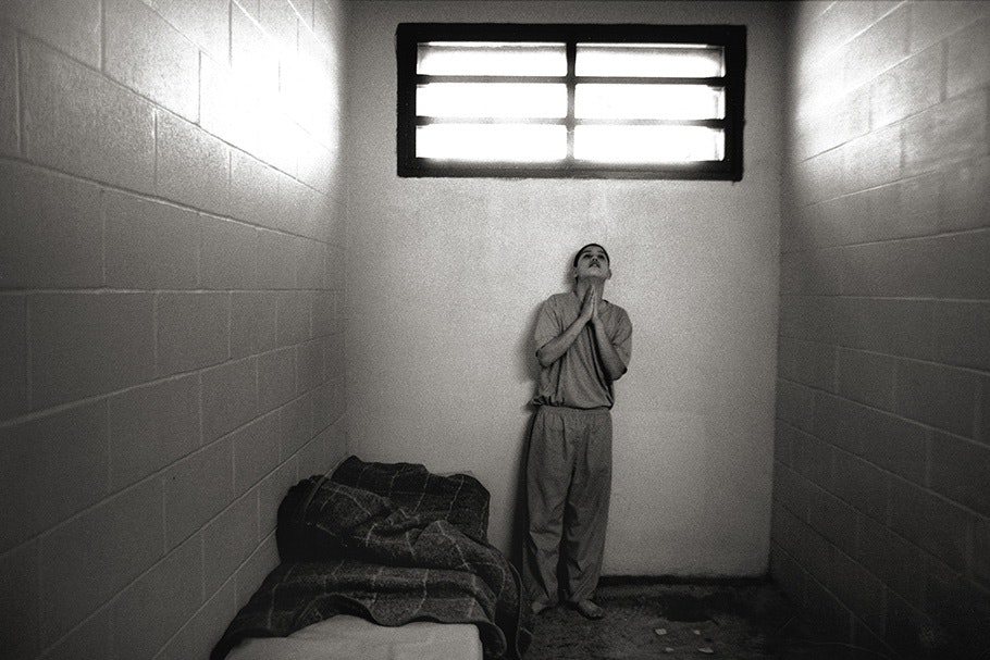 A boy praying in a cell with a small window above.