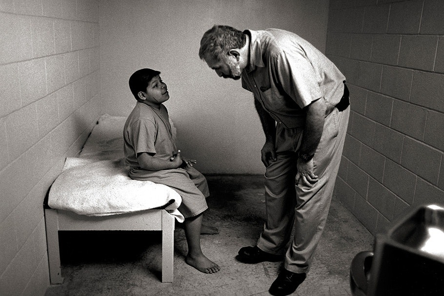 Guard talking to a young boy in a cell.