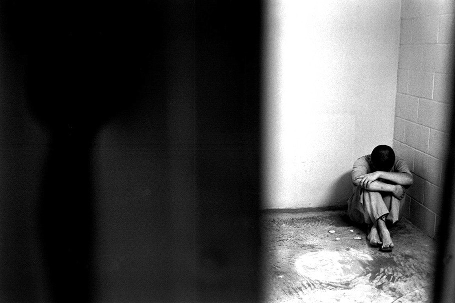 A boy curled up on the floor of a cell.