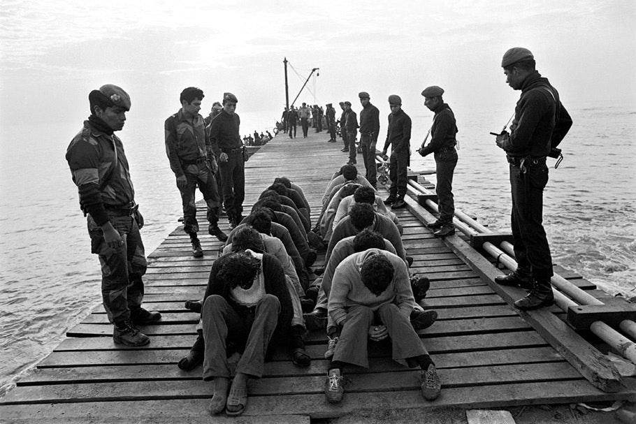 Soldiers and prisoners on a dock.
