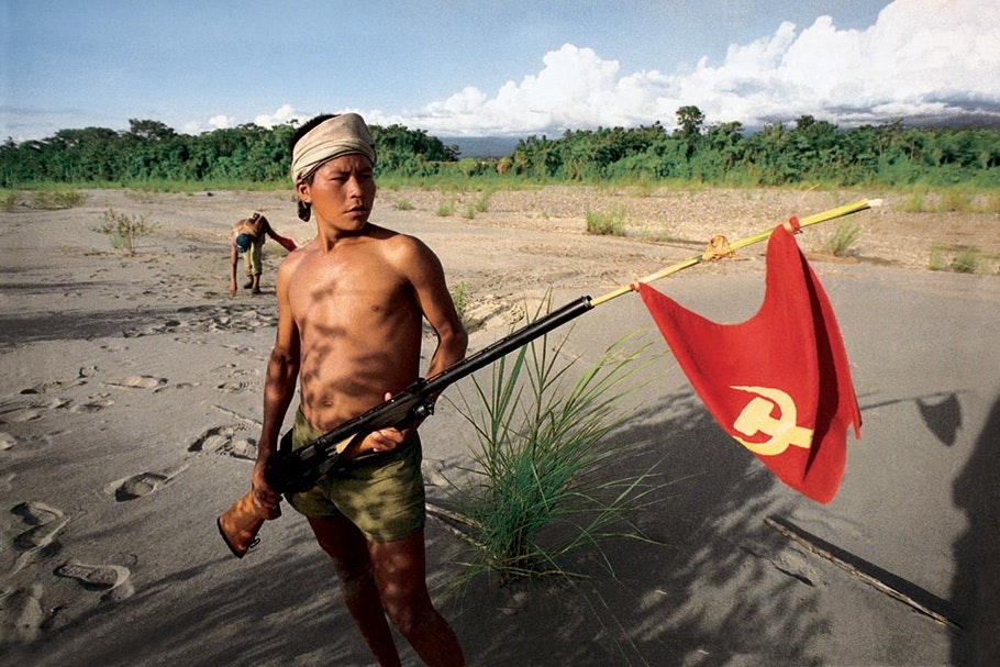 A young man holding a gun with a red flag.