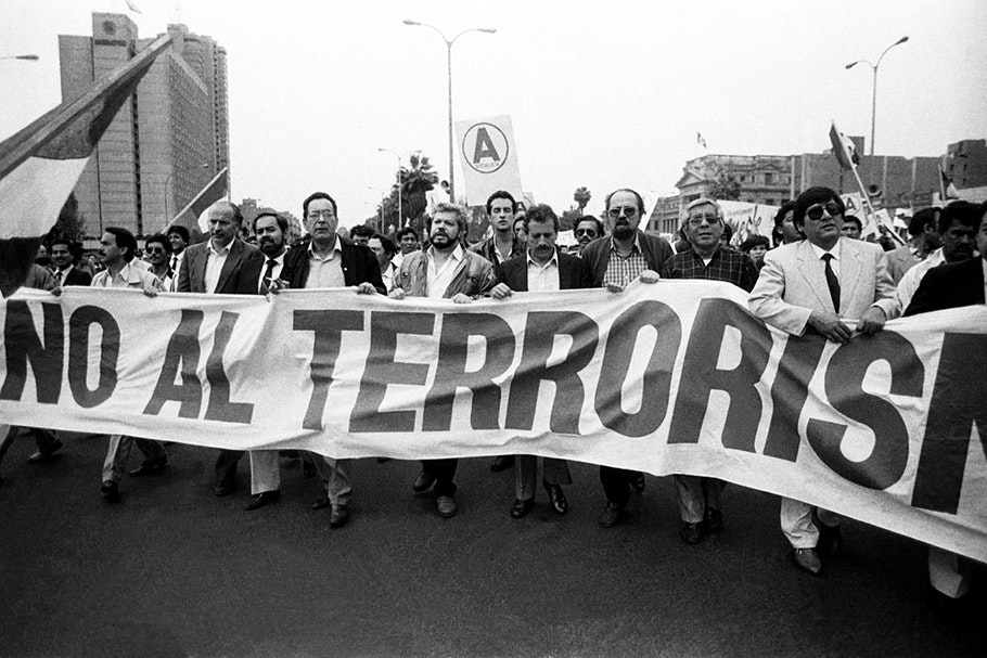 Demonstrators marching with a large sign.