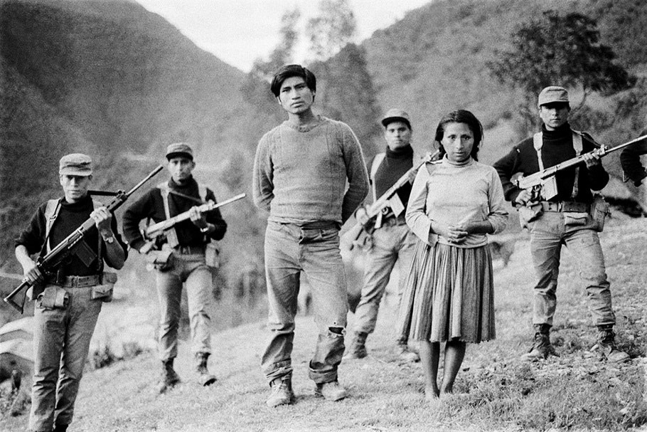 A couple surrounded by armed men.