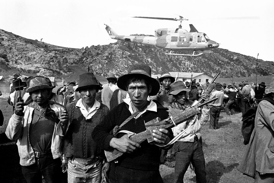 Armed men in front of a helicopter.