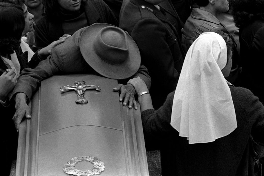 A man draped over a coffin.