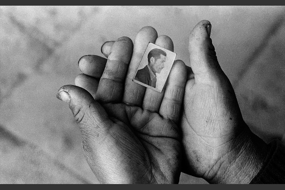 Hands holding a small portrait.